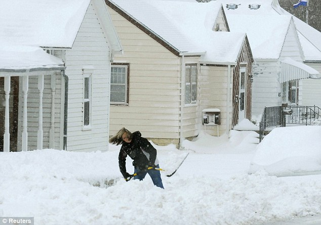 Stuck in: Debbie Weber digs out her driveway in Hays, Kansas, on Tuesday after a winter storm dumped more than 8 inches of snow on the area