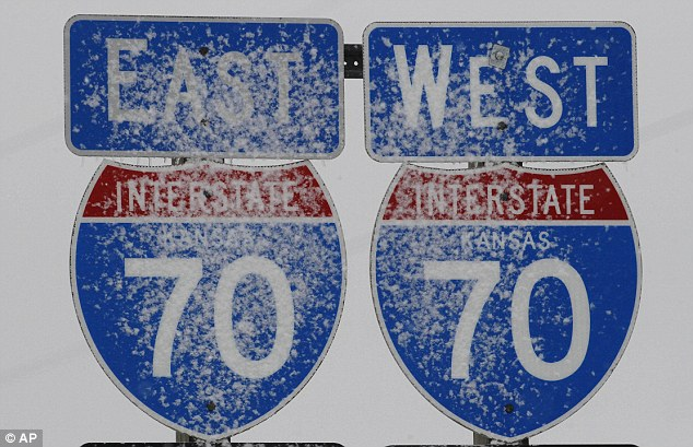 Way to go: Snow sticks to road signs along I-70 near Paxico, Kansas, on Tuesday. A deadly storm that halted travel throughout the Great Plains began to weaken on Tuesday