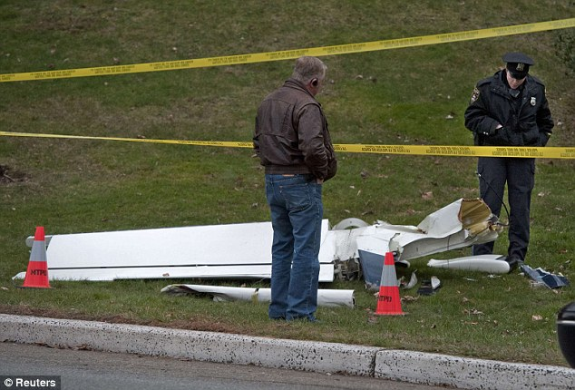 Inspection: Police officers examine the wreckage of the Socata plane after it crashed along Interstate Route 287