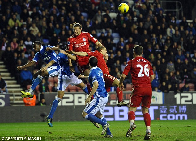 Missing the target: Substitute Andy Carroll jumps highest but fails to threaten the Wigan goal