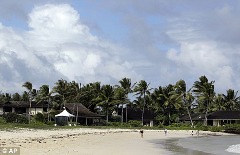 Holidays: People walk past a security tent along the beach at Kailua Bay near where first lady Michelle Obama and her daughters are staying in Kailua, Hawaii