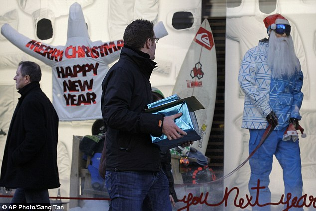 A man carrying gift-wrapped presents is distracted by goods in a shop window as the countdown to Christmas Day continues