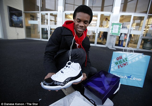 Happy: One lucky shopper at Lafayette Square Mall in Indianapolis, Indiana, shows off his purchase of Air Jordan 11 Retro shoes