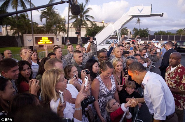 Finally here: The President shakes the hand of a young admirer in a Santa costume in Hawaii, the state where he grew up