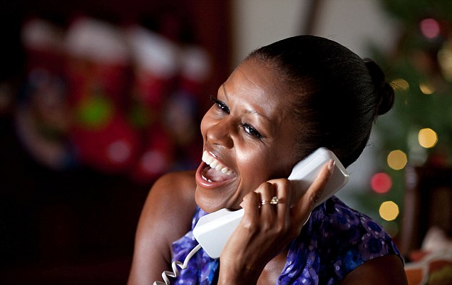 Santa's on his way: Michelle Obama talks on the phone to children across the U.S. as part of the annual NORAD Tracks Santa programme on Saturday