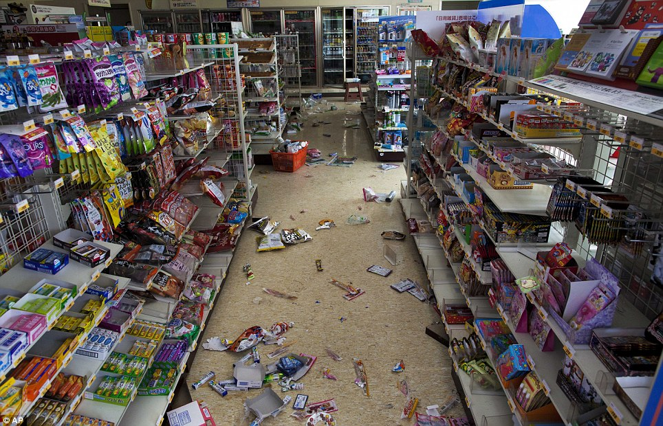 Poisoned: An abandoned basket of shopping can be seen in a grocery store in Futaba and packets of sweets litter the floor after the 9.0-magnitude quake struck
