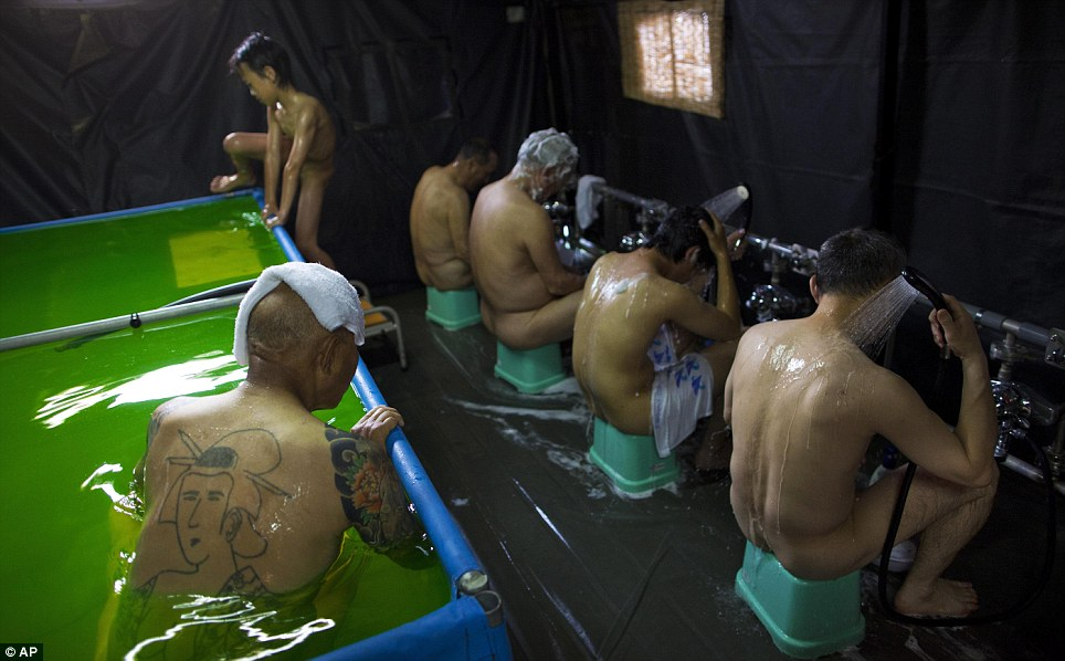 Precautions: One-time employees of the nuclear power plant bathe at an evacuation centre in Koriyama after being forced to abandon their homes within the exclusion zone