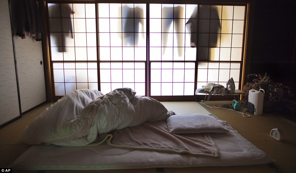 Running for their lives: A duvet is thrown back from a futon in an abandoned home less than three miles from the damaged Fukushima nuclear power plant