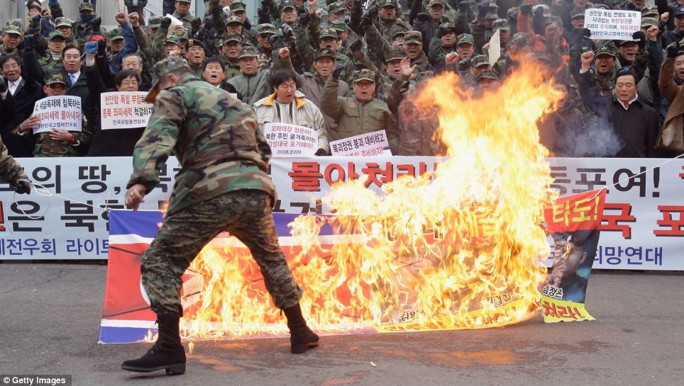 Rally: Across the border in South Korea, protesters have been burning the North Korean flag in protest at the succession of Kim Jong Un