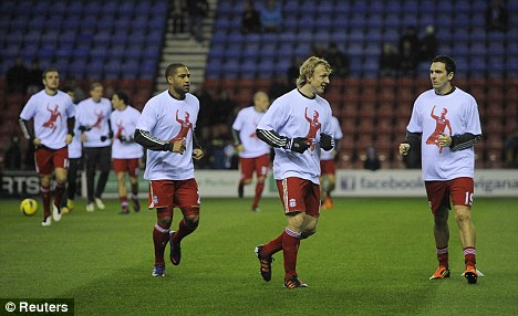 Show of support: Liverpool players donned Luis Suarez T-shirts before their 0-0 draw at Wigan