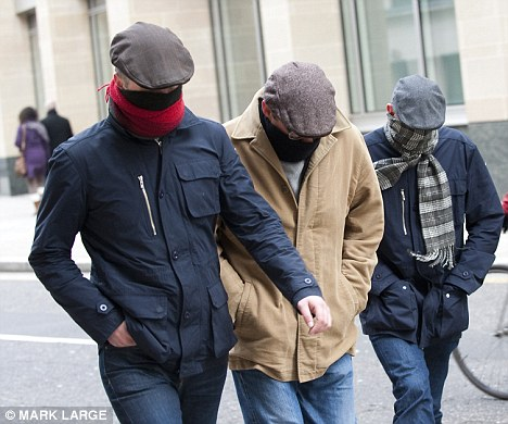 Hiding: Family or friends of the Norris family arrive at the Old Bailey with their faces hidden behind scarves for the sentencing of David Norris today