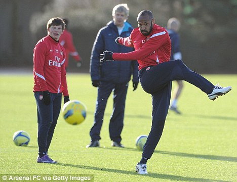 Shooting boots: Henry is watched by Arsene Wenger on Friday