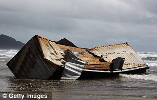 A washed up container containing wood lies at Waihi Beach