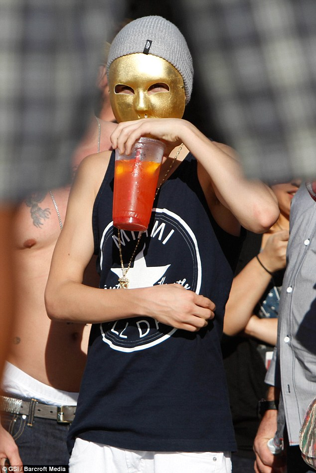 Quenching his thirst: The pop star didn't have any trouble sipping on a drink while wearing his mask