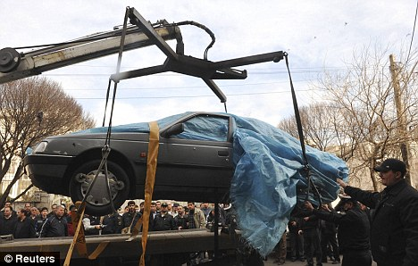 A crane lifts away the wreckage of Mr Roshan's car after he was killed by a magnetic bomb was attached to it