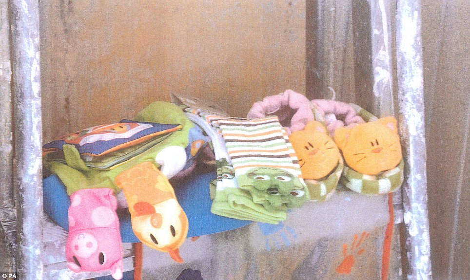 Despite the squalor elsewhere, Declands socks and slippers are arranged neatly beside toys and a fabric book on a shelf