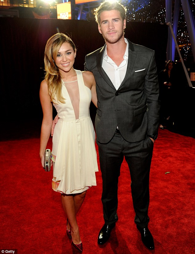 Glam couple: Miley Cyrus looked pleased as punch as she posed with her hunky actor boyfriend Liam Hemsworth