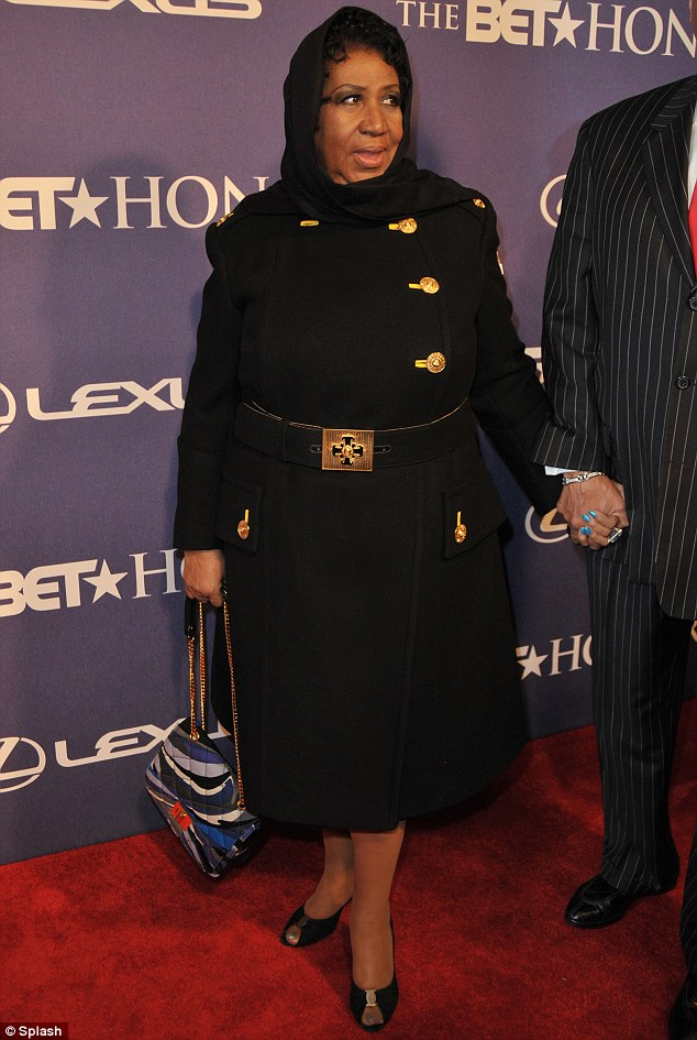 She's getting married! Aretha Franklin, 69, covered up in a big black and gold coat