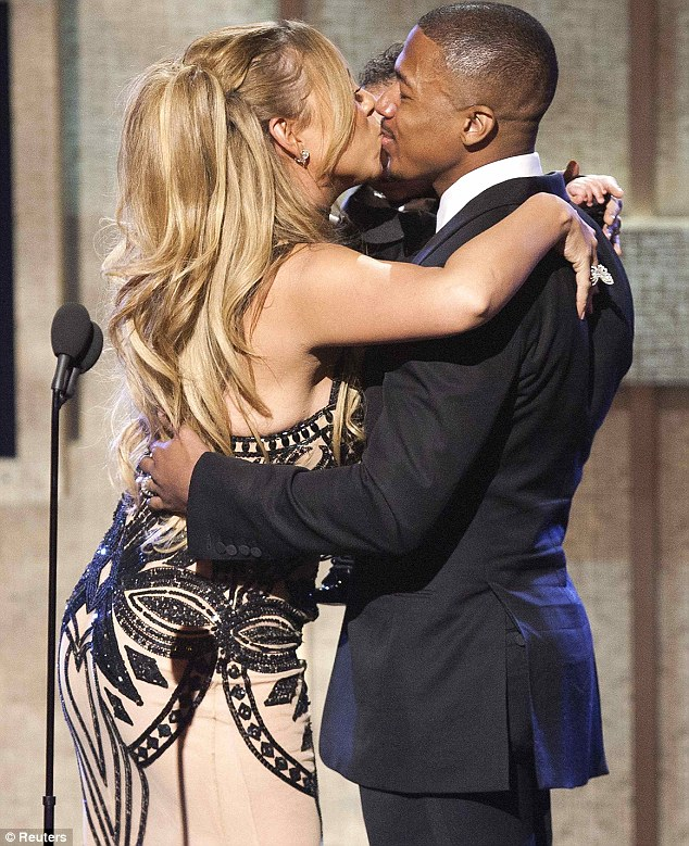 Pleased to have you back: Mariah kisses Nick on stage as she was honoured tonight
