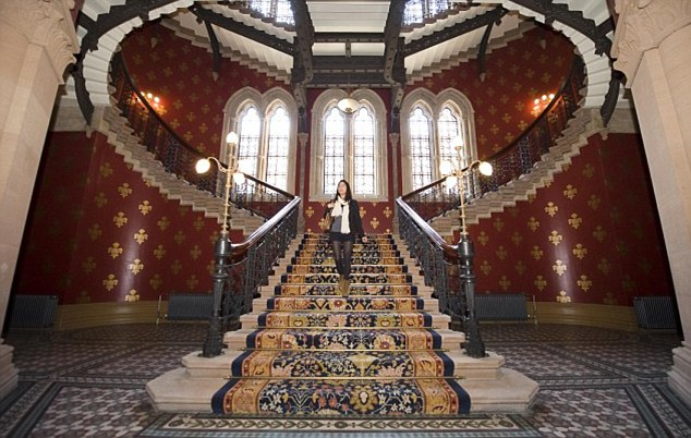 A woman is pictured walking down the Grand Staircase at the St Pancras Renaissance London Hotel