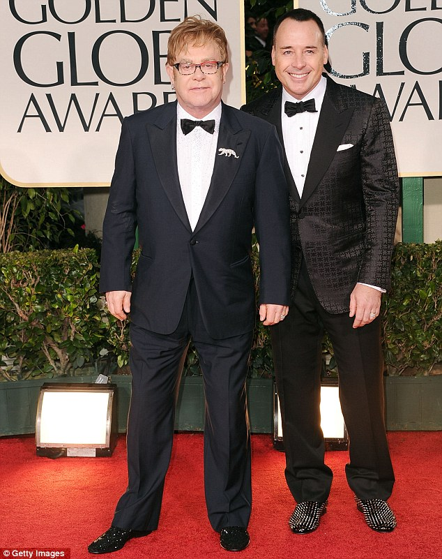 Catty: Elton John (pictured with David Furnish) and Madonna are nominated in the same category for Best Original Song