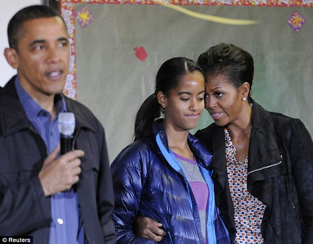 Pep talk: Michelle Obama (right) leans in and whispers something to Malia, probably attempting to lift her spirits as she appeared bored throughout her father's (left) speech at the MLK community service event