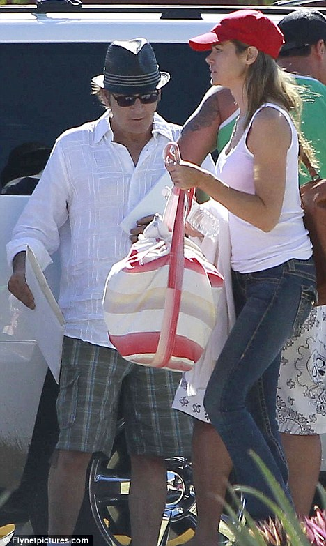 Modern family: Denise is seen here with Charlie earlier this week as the couple depart their resort in Mexico