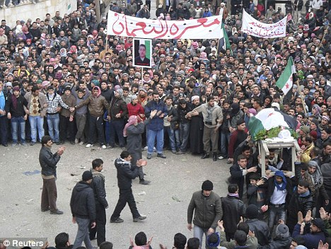 Defiance: Anti-government demonstrators carry the body of a protester, whom they claim was killed during clashes with troops in protests against President Bashar Al-Assad