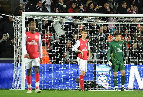 Disbelief: Arsenal players look on after falling behind to Swansea and in the race for the top four