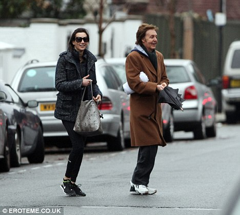 Happy times: Sir Paul and Nancy were all smiles in the rain in north London