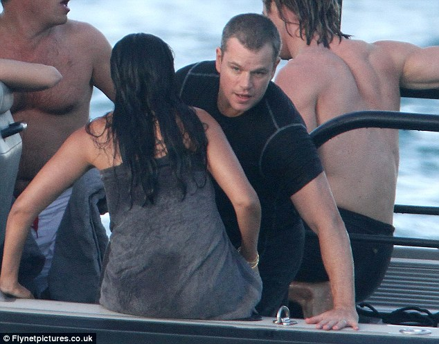Hello dear: Matt Damon balances himself as he moves over to sit down next to his wife Luciana