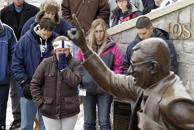 People gather around a statue outside Beaver Stadium on the Penn State University campus after learning of the coach's death