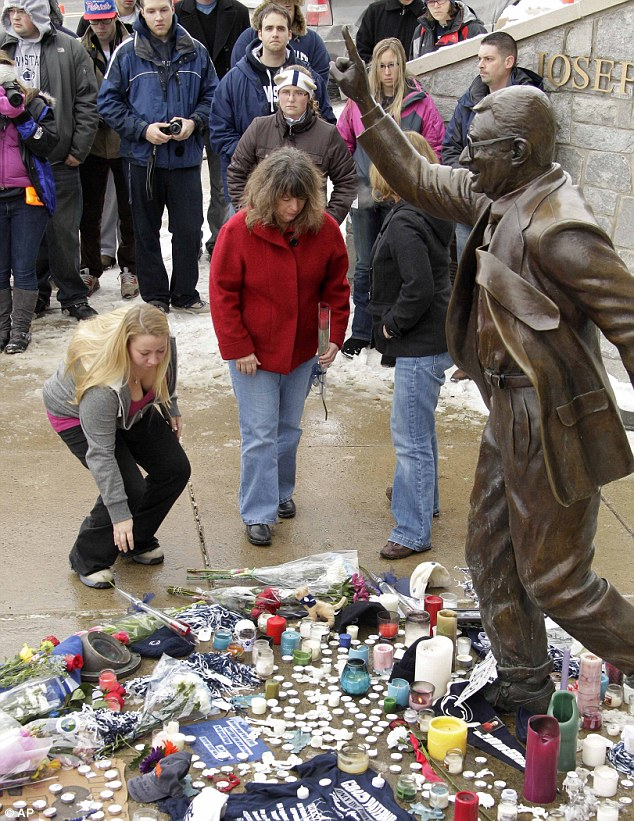 Mourners lay flowers at a statue of Joe Paterno in his memory