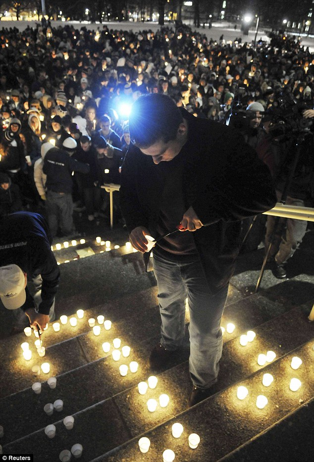 Tribute: Tyler Latsha, Penn State senior, from Northumberland, Pennsylvania, lights candles on the steps of Old Main at Penn State University