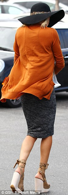 Going all out: She paired the dress with a long orange cardigan, floppy hat and massive wedges