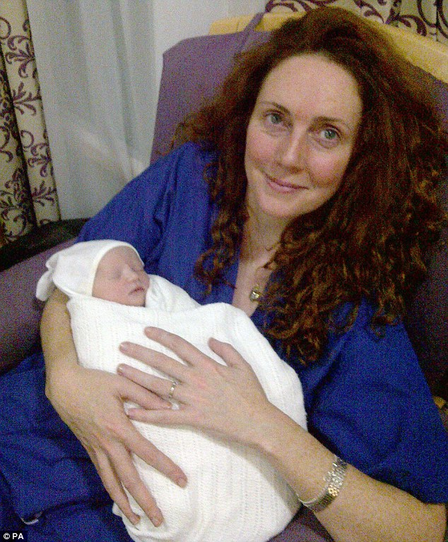 Delight: Former News International chief executive Rebekah Brooks cuddles baby daughter Scarlett Anne Mary who was born by surrogate mother in January 2012