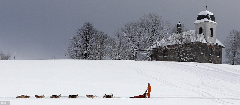 Winter scene: A musher passes this isolate church surounded by trees as he competes during Sedivackuv Long dog sled race