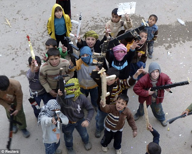 Caught in the middle: Boys hold toy weapons as they protest against Syria's President Bashar al-Assad in Homs