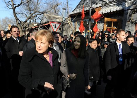 German Chancellor Angela Merkel tours Nanluo Guxiang in Beijing today on her visit to reassure China over the eurozone crisis