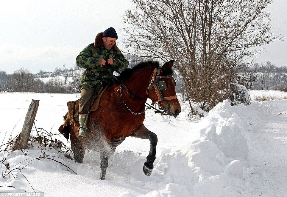 Horsepower: A man rides through snow in the village of Vrapce 300km south of Belgrade in Serbia