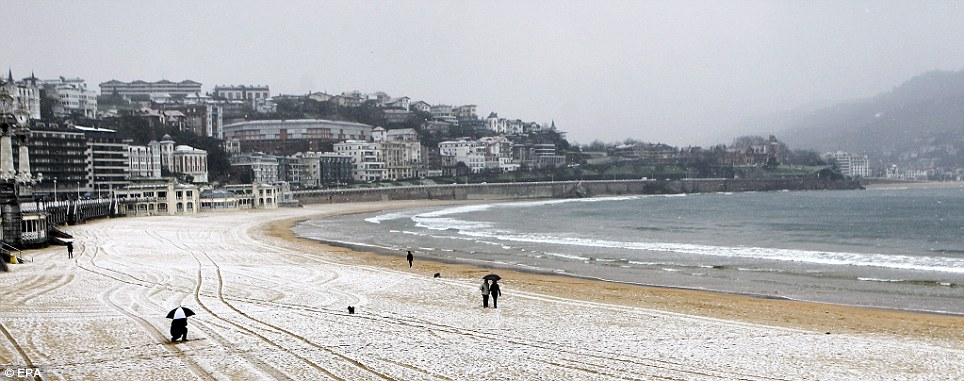 A thin layer of snow covers the sand on La Concha beach in San Sebastian, north Spain
