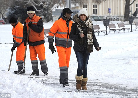 Workers clear snow as a pedestrian walks on a path in downtown Skopje, Macedonia