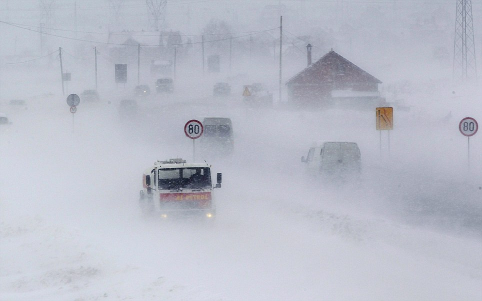 Harsh: A truck drives through heavy snow falls near the town of Obilic, Kosovo. 122 people have died across Eastern Europe since the cold snap began on Friday last week