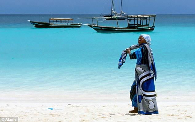 A woman wearing a kanga on the beach