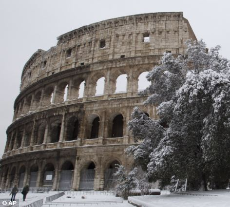 Snow surrounds the ancient Colosseum, in Rome