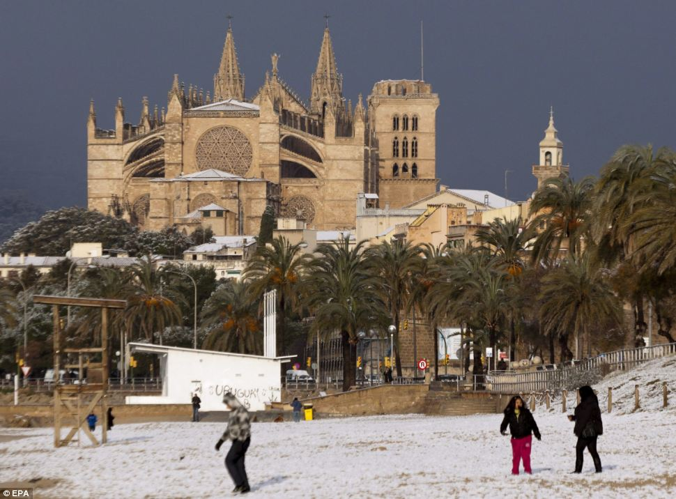 Slushy sand: Children play on a snow-covered beach near the Majorca's Cathedral in Palma, Majorca