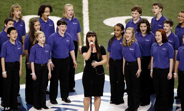 Kick off: Kelly marked the opening of the sports game as she sang The Star-Spangled Banner