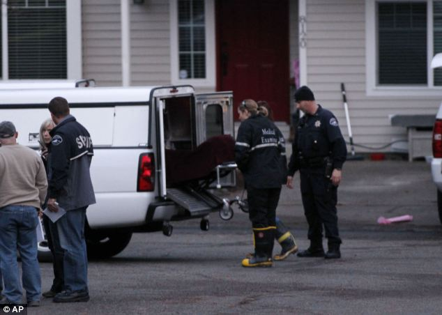 Day of anguish: Officials remove the first of three bodies from the remains of the house near in Graham, Washington state