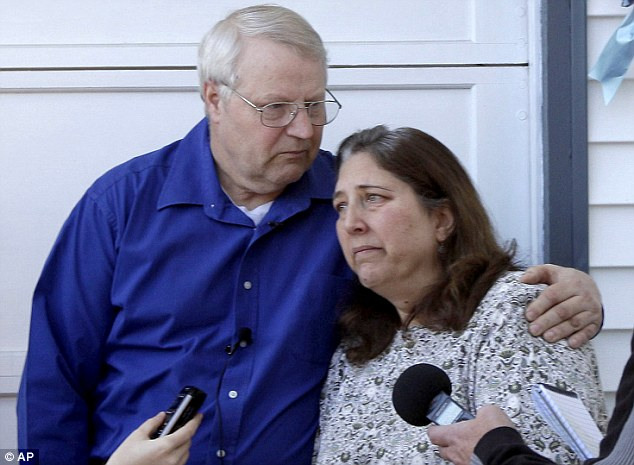 Grieving: Chuck and Judy Cox speak with reporters at their home in Puyallup, Washington. Chuck puts his arm around his wife as they fight back tears