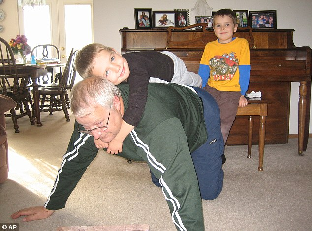 Loving grandfather: Chuck Cox plays with his grandsons, Charlie, right, and Braden, left, giving Charlie a piggy-back ride